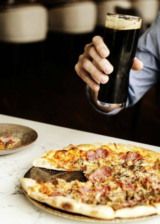 Man drinking a beer and eating a pizza at Tavola Italian Kitchen + Bar, Minneapolis